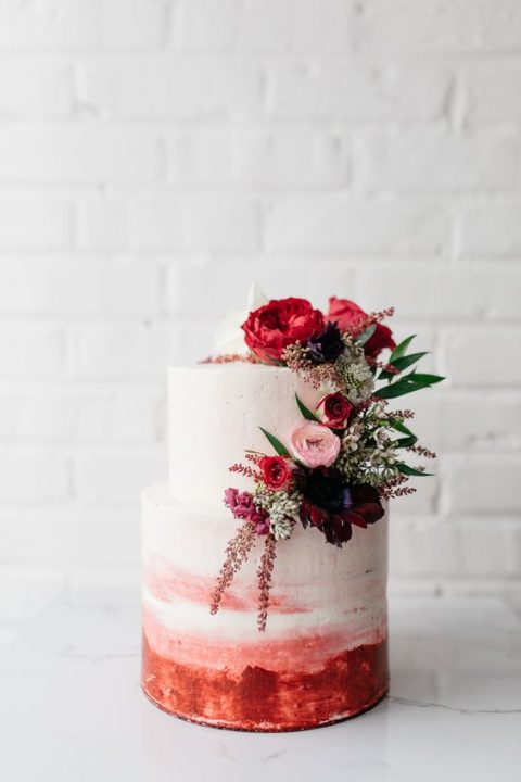 an ombre pink watercolor wedding cake topped with pink and red blooms and greenery