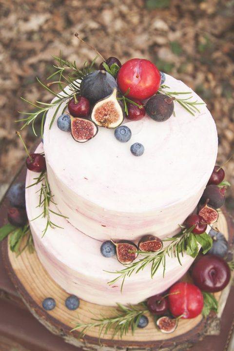an ombre pink wedding cake topped with fresh herbs and fresh fruits and berries