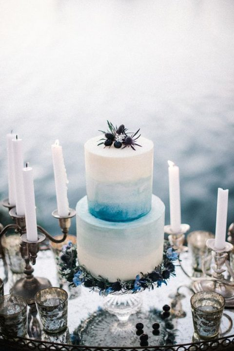 buttercream is ideal for decorating the cake with watercolor, here an ombre blue wedding cake with blueberries and thistles