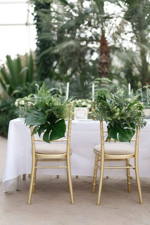chairs decorated with ferns and large monstera leaves