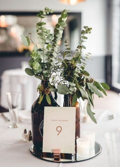 dark glass bottles with fresh eucalyptus, a mirror tray, some candles and a table number