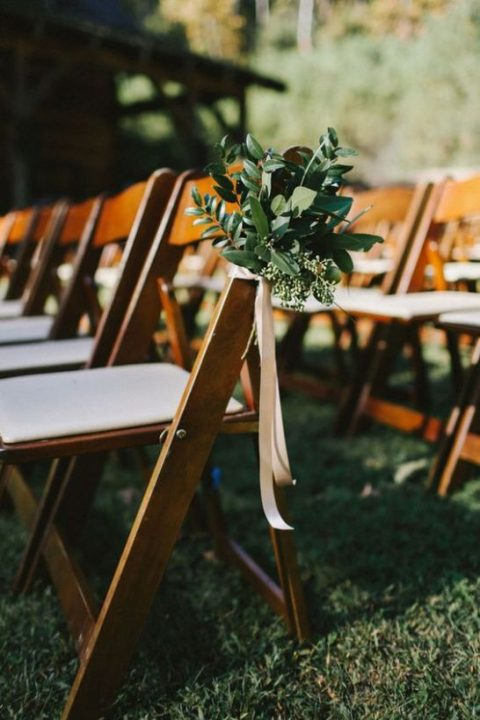 decorate your wedding aisle chairs with textural greenery and ribbons