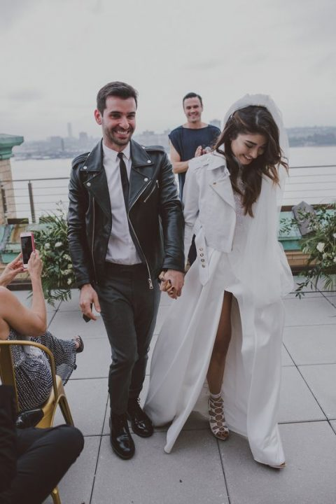 grey pants, a white shirt, a black leather moto jacket, black shoes for a modern groom_s look