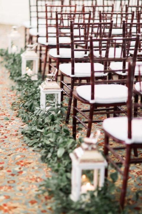 lush greenery along the wedding aisle and white lanterns for a fresh look