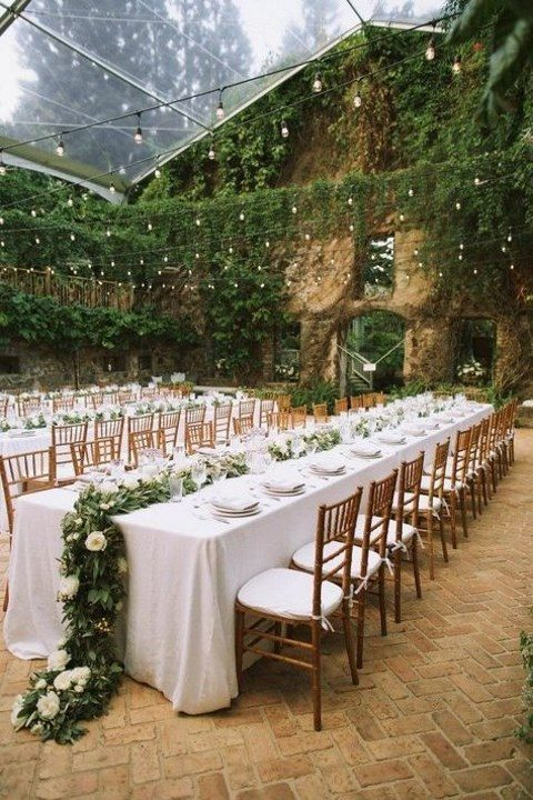 lush greenery over the reception space and lights to refresh the wedding reception space