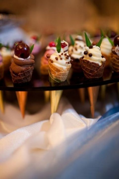 mini ice cream cones with fresh berries on top and some greenery