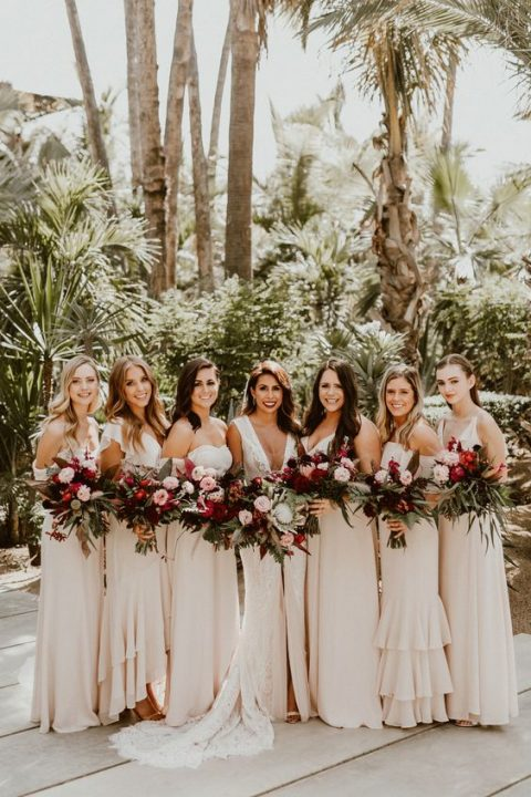 mismatching ivory bridesmaid maxi dresses with ruffles in various places