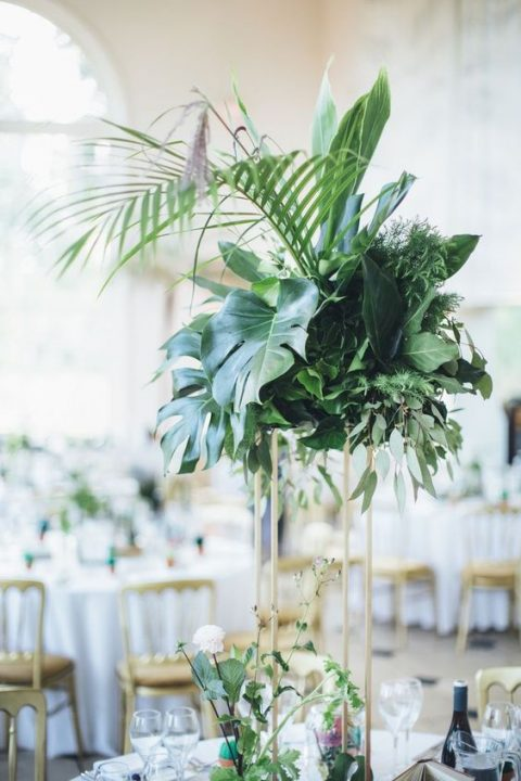 monstera leaves, cordyline and areca palms with ivy, grass and eucalyptus on a tall geo stand