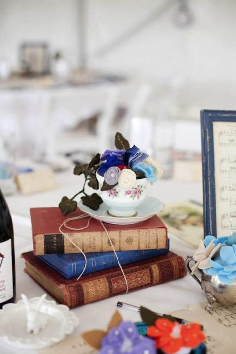 a bright book centerpiece with a vintage teacup and fabric blooms and leaves
