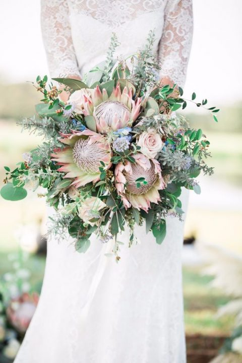 a bright king protea wedding bouquet with blue and blush blooms, greenery and herbs