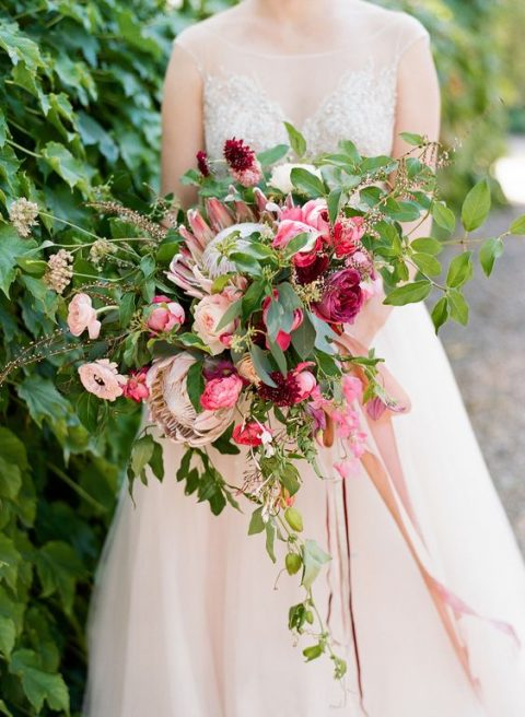 a bright summer wedding bouquet with king proteas, bright pink flowers and much greenery