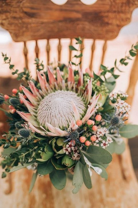 a bright wedding bouquet with a king protea, blooms, berries, thistles and greenery