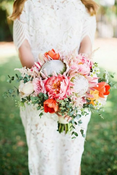 a bright wedding bouquet with pink peonies, king proteas, orange tulips and greenery