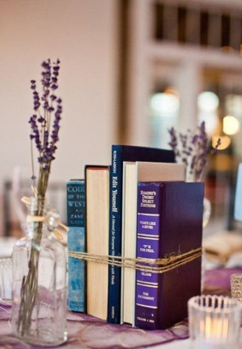 a bundled books centerpiece with some candles and lavender around