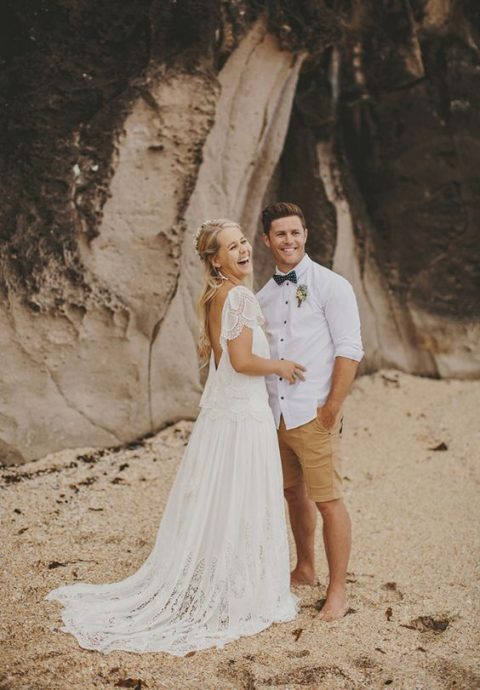 a casual groom_s look with ocher shorts, a white shirt with pulled up sleeves and a bow tie