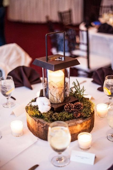a centerpiece made of a wood slice with moss, pincones, cotton and a modern metal candle lantern