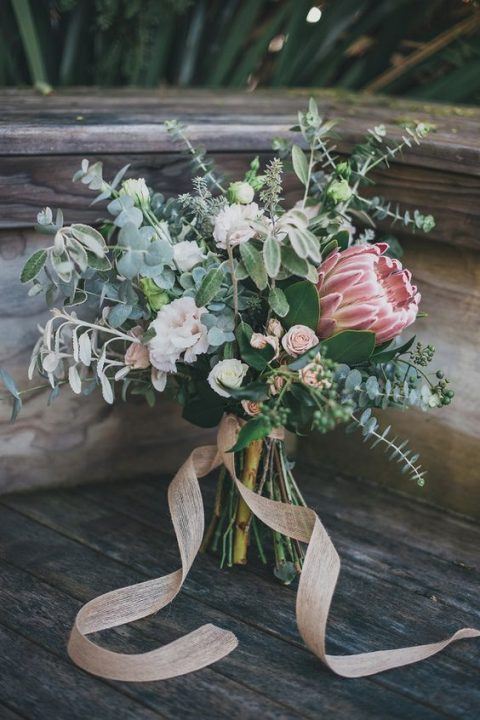 a chic wedding bouquet with a king protea, little blooms, greenery, blush ribbons
