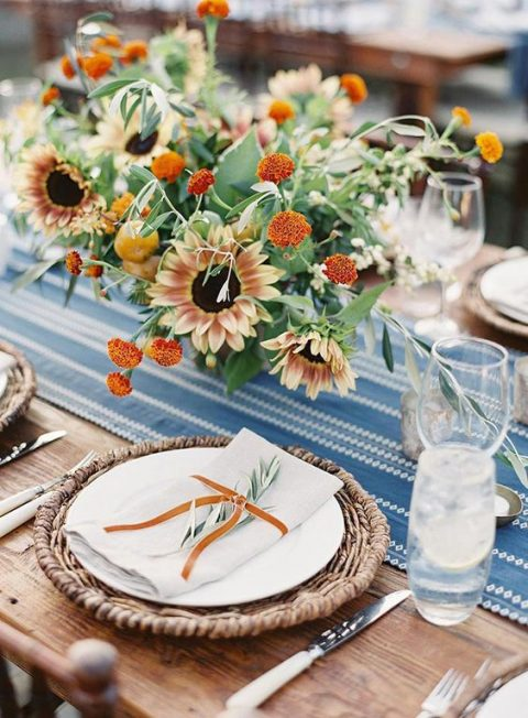 a colorful rustic rehearsal dinner with printed table runners, a bright bloom centerpiece, wicker chargers and rust touches