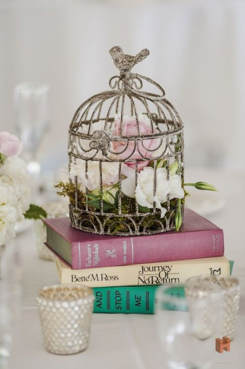 a cool book centerpiece with a stack of books, a vintage cage with moss and blooms