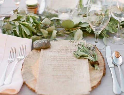 a cozy and chic rustic place setting with a wood slice, a greenery runner and pebble place cards