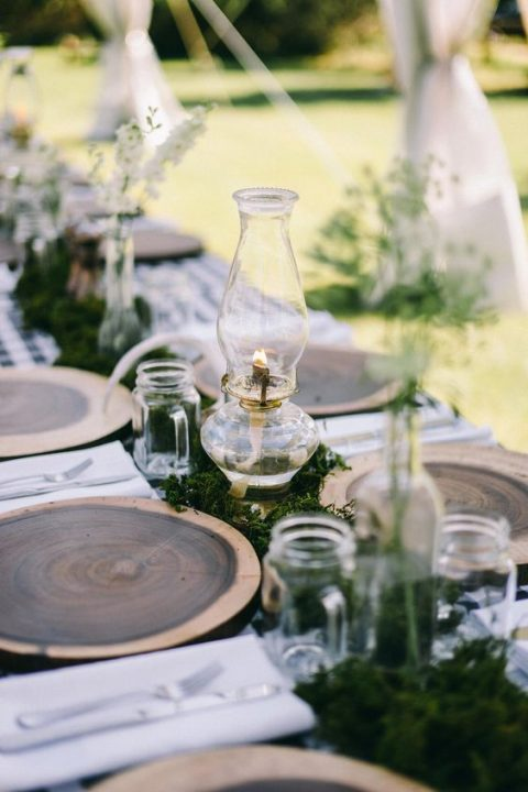 a cozy rustic or woodland tablescape with stained wood slices, moss, lanterns and jar mugs