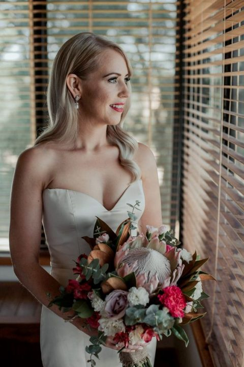 a creative bridal bouquet with a king protea, hot pink and lilac blooms, greenery and magnolia leaves