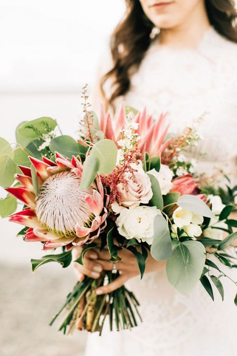 a delicate wedding bouquet with king proteas, blush and white blooms and greenery