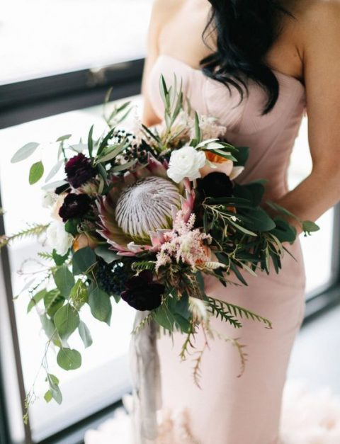 a dramatic wedding bouquet with a single king protea, blush and purple blooms, greenery and herbs