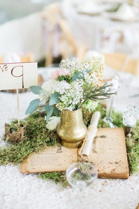 a fairy-tale centerpiece with moss, a vintage opened book, a gilded vase with blooms and greenery, a table number