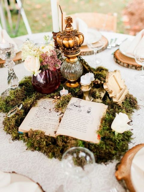 a fairy-tale centerpiece with moss, an opened book, candles, a crown on a stand and some blooms