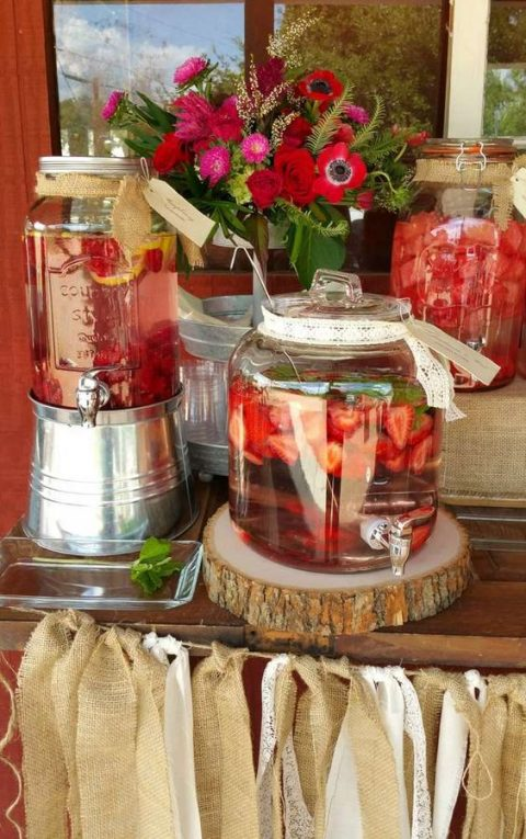 a flavored water station decorated with blooms and a burlap tassel garland for a country chic rehearsal dinner party