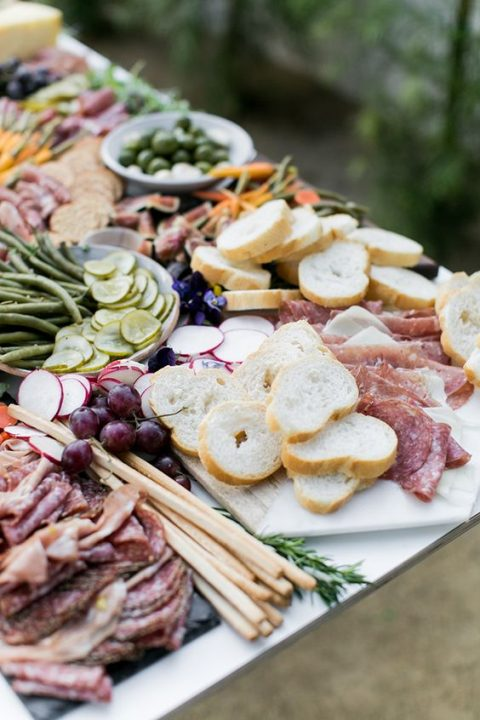 a gorgeous charcuterie table with veggies, salamis and bread