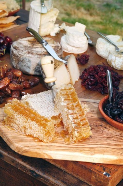 a grazing table with cheeses, fruits and dried fruits and honeycombs