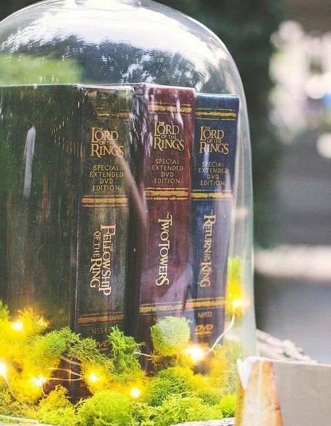 a large cloche with moss, LED lights and LOTR books