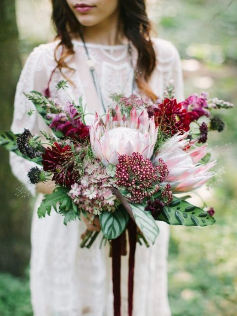 a lush and bright wedding bouquet with king proteas, burgundy flowers and bold leaves