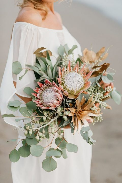 a lush fall wedding bouquet with gilded succulents, greenery, king proteas and acorns