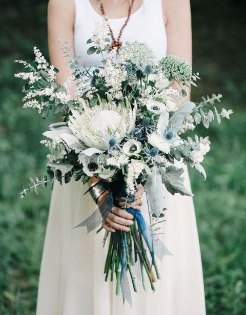 a neutral wedding bouquet with a king protea, white anemones, blue thistles, eucalyptus and herbs