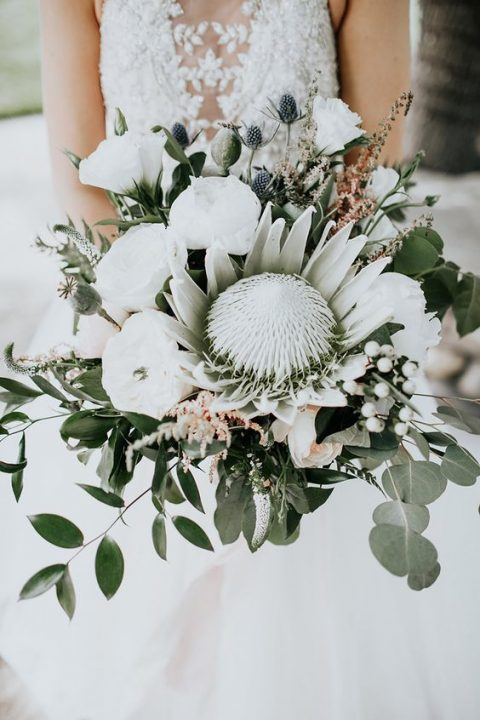 a pure white wedding bouquet with white blooms, a king protea, berries, thistles and greenery