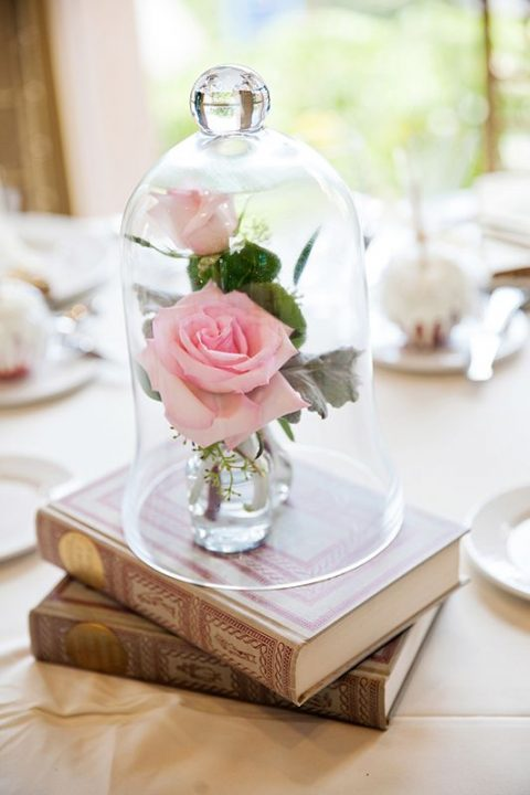 a romantic and refined wedding centerpiece with a couple of books plus pink roses in vases and a cloche