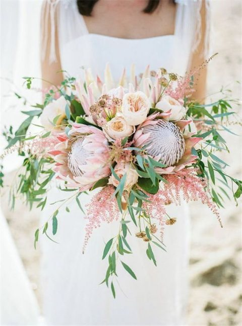 a romantic wedding bouquet with blush blooms, king proteas, cascading greenery