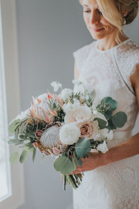 a romantic wedding bouquet with king proteas, blush and white blooms, eucalyptus