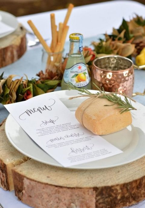 a rustic place setting with a wood slice, a copper mug and bread with greenery