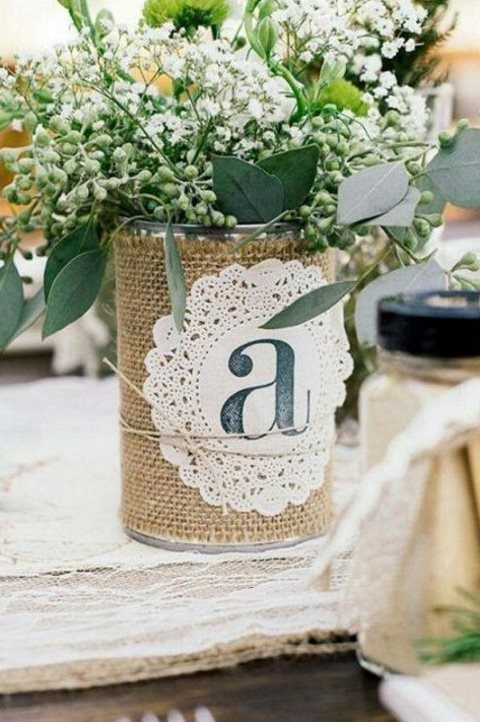 a rustic rehearsal dinner centerpiece of a tin can wrapped with burlap, a doily and baby_s breath