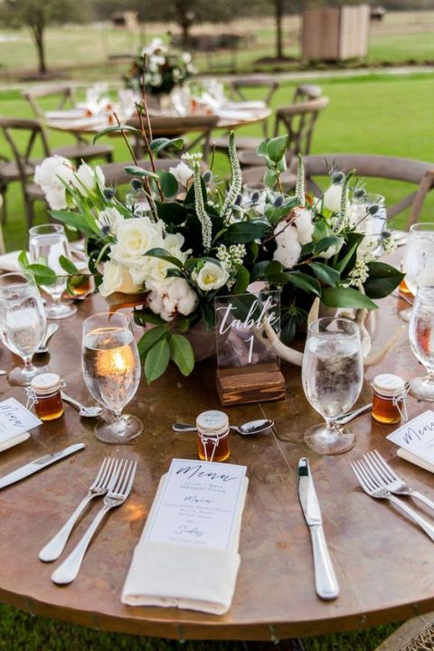 a rustic rehearsal dinner table setting with honey favors, a lush white bloom centerpiece and an uncovered table