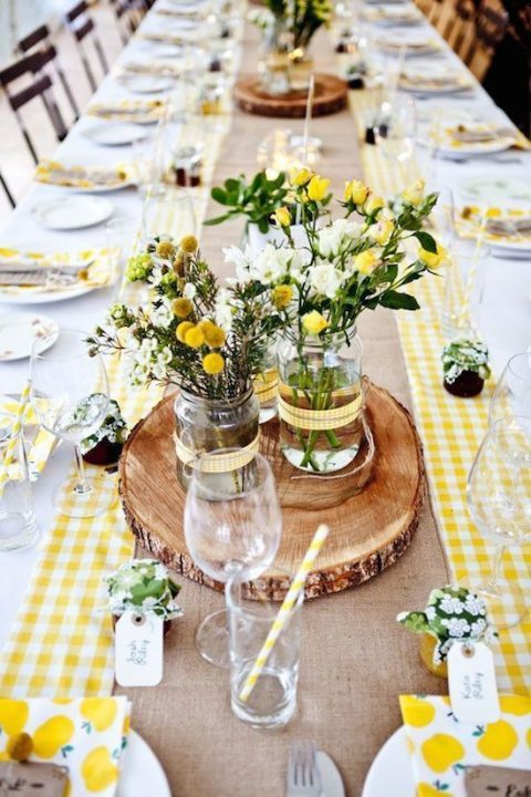a rustic rehearsal dinner tablescape with yellow checked runners, a burlap one, wood slices and brigth yellow touches
