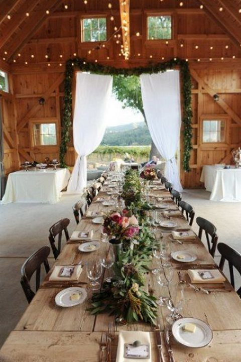 a rustic table setting with colorful bloom and greenery centerpieces and an uncovered long table