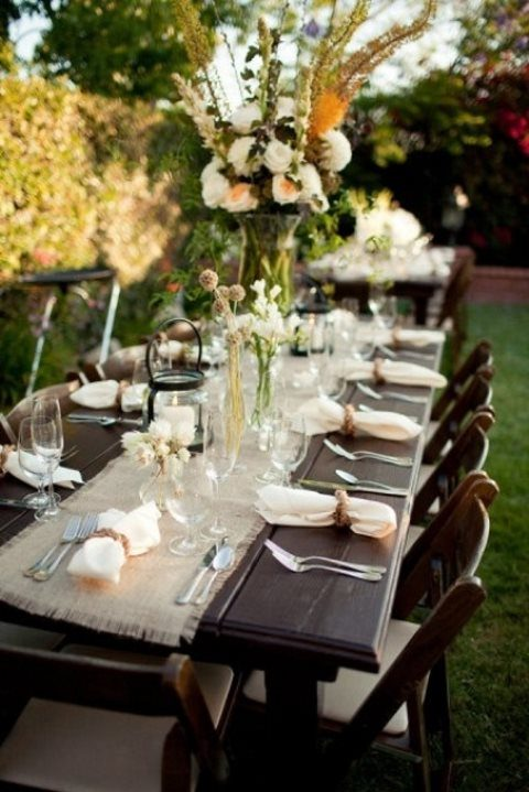 a rustic tablescape with white and yellow blooms and a burlap runner, candle lanterns and twine napkin rings