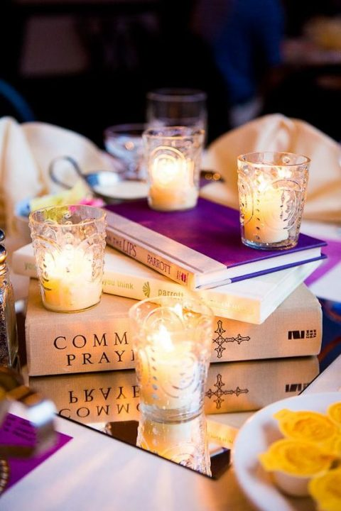 a simple centerpiece of a mirror, a stack of books and candles in glasses