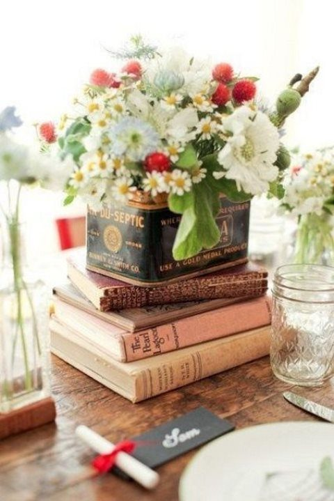 a simple centerpiece with a stack of books, a tin can with blooms and greenery