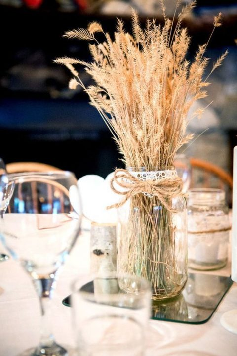 a simple rustic centerpiece with a mirror, a jar with wheat and twine and lace
